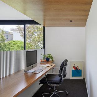 メルボルンの小さいコンテンポラリースタイルのおしゃれなホームオフィス・仕事部屋 (白い壁、カーペット敷き、造り付け机、黒い床) の写真
