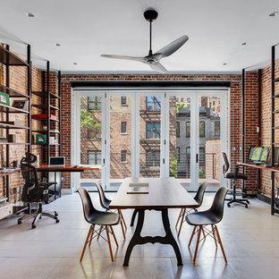 Aménagement d'un grand bureau industriel avec un mur rouge, aucune cheminée, un bureau intégré et un sol blanc.