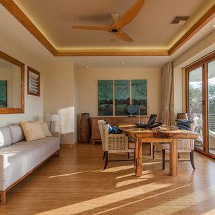 Idee per un grande studio tropicale con pareti beige, pavimento in bambù, scrivania autoportante e pavimento beige