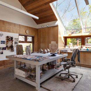 На фото: домашняя мастерская в современном стиле с коричневыми стенами, бетонным полом, отдельно стоящим рабочим столом, серым полом, сводчатым потолком и деревянными стенами