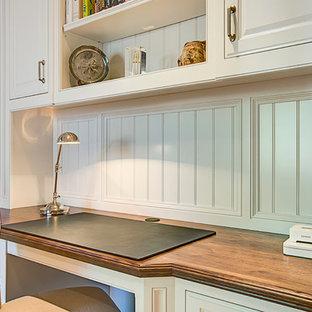 Idéer för mellanstora amerikanska hemmabibliotek, med beige väggar, heltäckningsmatta, ett inbyggt skrivbord och beiget golv