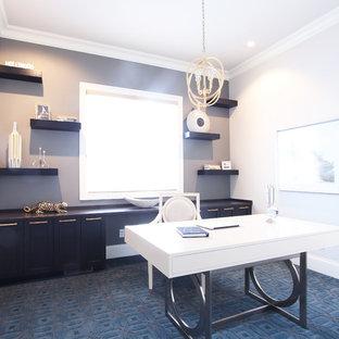 Пример оригинального дизайна: кабинет среднего размера в стиле неоклассика (современная классика) с серыми стенами, ковровым покрытием, отдельно стоящим рабочим столом и синим полом