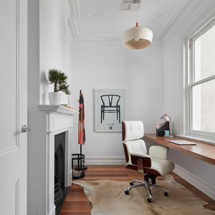 Inspiration for a small contemporary built-in desk medium tone wood floor home office remodel in Melbourne with white walls and a standard fireplace