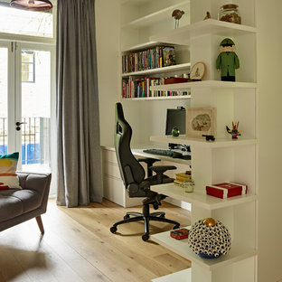 Medium sized contemporary study in London with white walls, light hardwood flooring, a freestanding desk and beige floors.