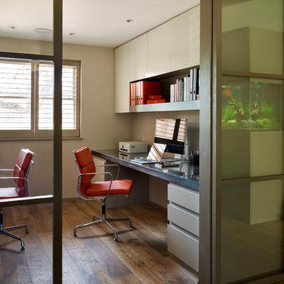 Trendy built-in desk dark wood floor study room photo in London with no fireplace