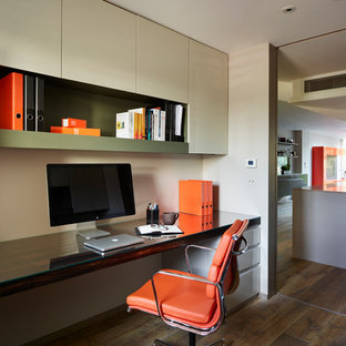 Design ideas for a contemporary study in London with a built-in desk and dark hardwood flooring.