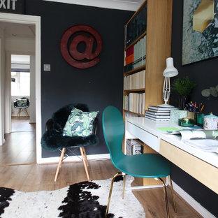 サリーの小さいエクレクティックスタイルのおしゃれな書斎 (黒い壁、ラミネートの床、自立型机、茶色い床) の写真