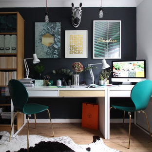 Immagine di un ufficio bohémian con pareti nere, pavimento in laminato, scrivania autoportante e pavimento marrone