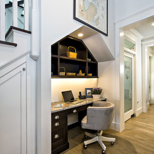 Inspiration for a small timeless built-in desk medium tone wood floor home office remodel in Miami with white walls