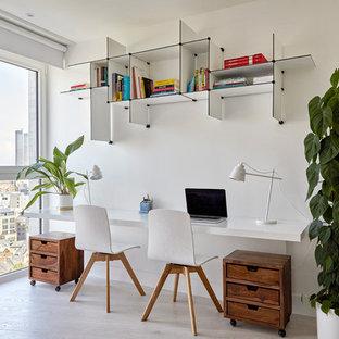На фото: рабочие места в скандинавском стиле с белыми стенами, светлым паркетным полом, встроенным рабочим столом и бежевым полом