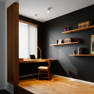 Mid-sized contemporary study room in Adelaide with black walls, a built-in desk, brown floor and light hardwood floors.