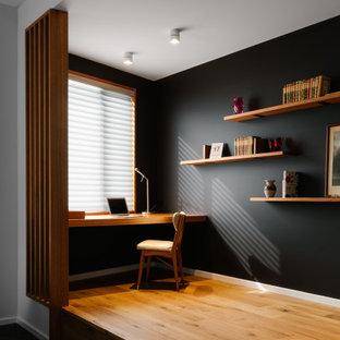 Exempel på ett mellanstort modernt hemmabibliotek, med svarta väggar, ett inbyggt skrivbord, brunt golv och ljust trägolv