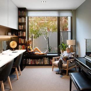 Inredning av ett modernt arbetsrum, med grå väggar, heltäckningsmatta, ett inbyggt skrivbord och grått golv