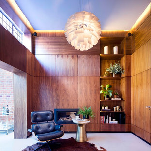 This is an example of a medium sized midcentury home office in London with brown walls, concrete flooring and a ribbon fireplace.