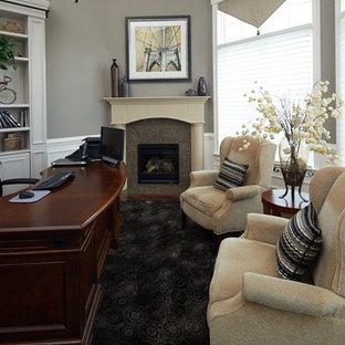 フィラデルフィアの大きいおしゃれなホームオフィス・書斎 (グレーの壁、カーペット敷き、コーナー設置型暖炉、タイルの暖炉まわり、自立型机、黒い床) の写真