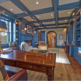 Idee per un grande ufficio classico con pareti blu, pavimento in legno massello medio, camino classico, cornice del camino in pietra, scrivania autoportante e pavimento marrone