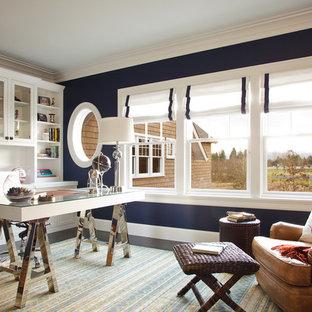Diseño de despacho costero, grande, con paredes azules, suelo de madera oscura, escritorio independiente, chimenea de doble cara y marco de chimenea de madera