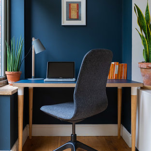 Small bohemian study in London with blue walls, medium hardwood flooring and a freestanding desk.