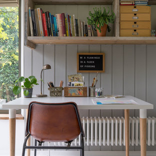 This is an example of a bohemian home office and library in London with a reading nook, grey walls and a freestanding desk.