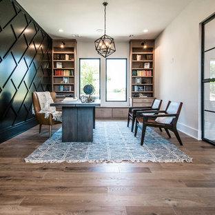 他の地域の大きいコンテンポラリースタイルのおしゃれなホームオフィス・仕事部屋 (白い壁、無垢フローリング、自立型机、茶色い床、暖炉なし) の写真