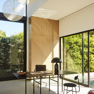 Inspiration for a modern freestanding desk concrete floor and gray floor home office remodel in Los Angeles with white walls