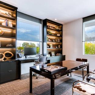 На фото: кабинет в современном стиле с белыми стенами, ковровым покрытием, отдельно стоящим рабочим столом и разноцветным полом без камина с