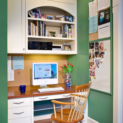 Example of a small classic built-in desk medium tone wood floor and brown floor study room design in Boston with green walls and no fireplace