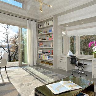 Exempel på ett mycket stort modernt hemmabibliotek, med grå väggar, skiffergolv, ett inbyggt skrivbord och grått golv