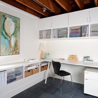 Идея дизайна: маленькое рабочее место в современном стиле с белыми стенами, полом из сланца и отдельно стоящим рабочим столом
