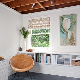 Inspiration för små moderna hemmabibliotek, med vita väggar, skiffergolv, ett fristående skrivbord och grått golv
