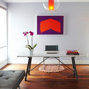 Foto di uno studio contemporaneo con pareti viola, parquet scuro e scrivania autoportante