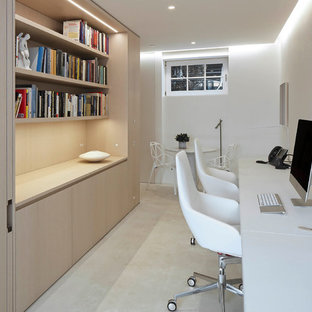 Example of a minimalist concrete floor study room design in New York with white walls