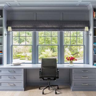 ニューヨークの中くらいのトラディショナルスタイルのおしゃれな書斎 (グレーの壁、淡色無垢フローリング、暖炉なし、造り付け机、茶色い床) の写真