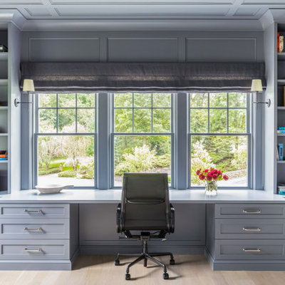 Example of a mid-sized classic built-in desk light wood floor and brown floor study room design in New York with gray walls and no fireplace