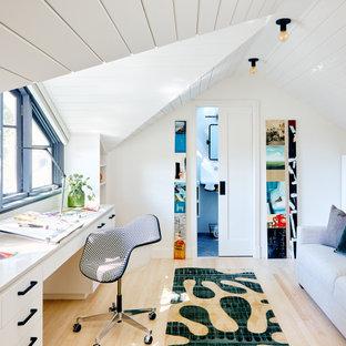 Idéer för ett modernt arbetsrum, med vita väggar, ljust trägolv, ett inbyggt skrivbord och beiget golv