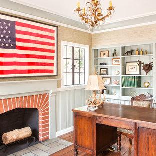 Lantlig inredning av ett arbetsrum, med beige väggar, mörkt trägolv, en standard öppen spis, en spiselkrans i tegelsten, ett fristående skrivbord och brunt golv