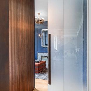 Idéer för funkis hemmabibliotek, med blå väggar, en dubbelsidig öppen spis, en spiselkrans i sten och ett inbyggt skrivbord