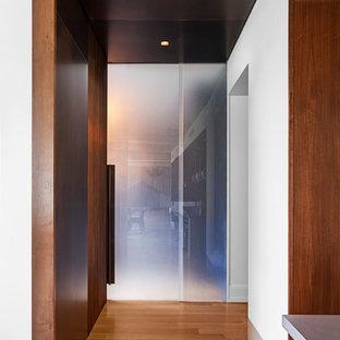 Imagen de despacho minimalista con paredes azules, chimenea de doble cara, marco de chimenea de piedra y escritorio empotrado