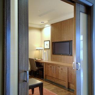 Foto di uno studio minimal con pareti beige, pavimento in legno massello medio e scrivania incassata