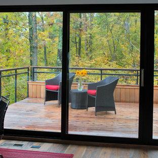 ミネアポリスの中サイズのモダンスタイルのおしゃれな書斎 (白い壁、無垢フローリング、横長型暖炉、漆喰の暖炉まわり、自立型机、茶色い床) の写真