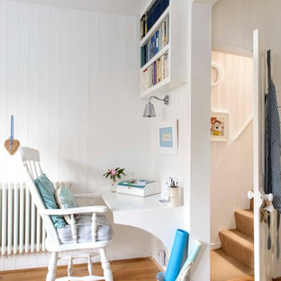 Home office - small beach style built-in desk medium tone wood floor home office idea in Kent with white walls