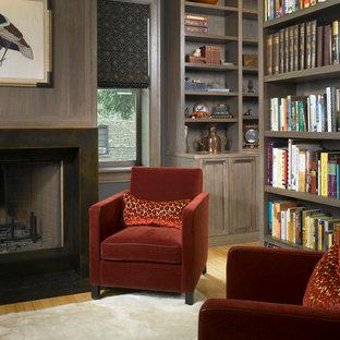 Diseño de despacho tradicional, de tamaño medio, con paredes grises, suelo de madera clara, chimenea tradicional y marco de chimenea de metal