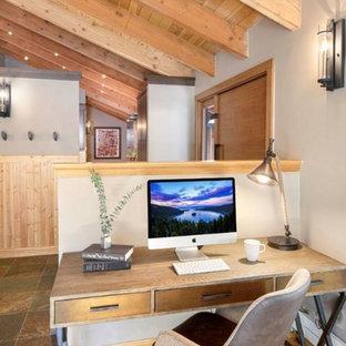 Bild på ett litet funkis arbetsrum, med beige väggar, ljust trägolv, en dubbelsidig öppen spis, en spiselkrans i sten, ett fristående skrivbord och brunt golv