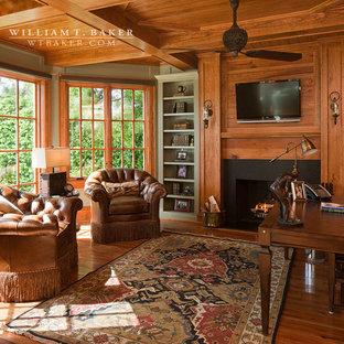 アトランタの中くらいのトラディショナルスタイルのおしゃれなホームオフィス・書斎 (茶色い壁、無垢フローリング、標準型暖炉、自立型机、ライブラリー、木材の暖炉まわり、茶色い床) の写真
