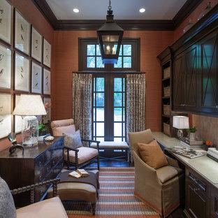 Idee per un ufficio tradizionale di medie dimensioni con scrivania incassata, pareti arancioni e parquet scuro