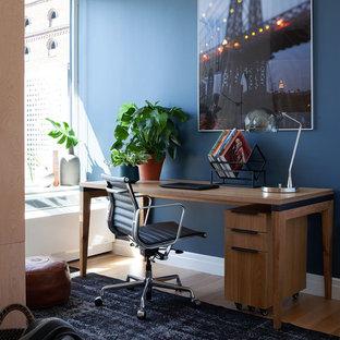 ニューヨークのインダストリアルスタイルのおしゃれな書斎 (青い壁、暖炉なし、自立型机、淡色無垢フローリング) の写真
