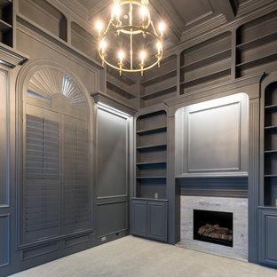 На фото: кабинет среднего размера в стиле современная классика с библиотекой, серыми стенами, ковровым покрытием, стандартным камином, фасадом камина из камня, отдельно стоящим рабочим столом и серым полом с