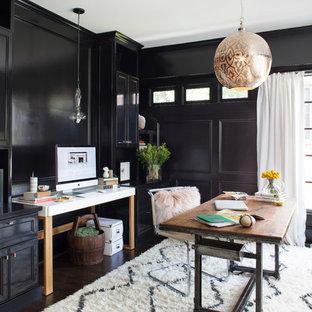Klassisk inredning av ett mellanstort hemmabibliotek, med svarta väggar, mörkt trägolv och ett fristående skrivbord