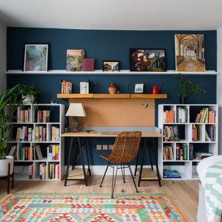 Mittelgroßes Modernes Arbeitszimmer mit Arbeitsplatz, hellem Holzboden, freistehendem Schreibtisch, weißer Wandfarbe und beigem Boden in London