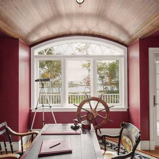 Uriges Arbeitszimmer ohne Kamin mit Arbeitsplatz, roter Wandfarbe, freistehendem Schreibtisch und hellem Holzboden in Portland Maine